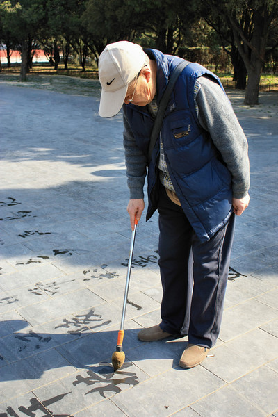 Chinese man writing with water in the entrance park are to the Temple of Heaven in Beijing, China.