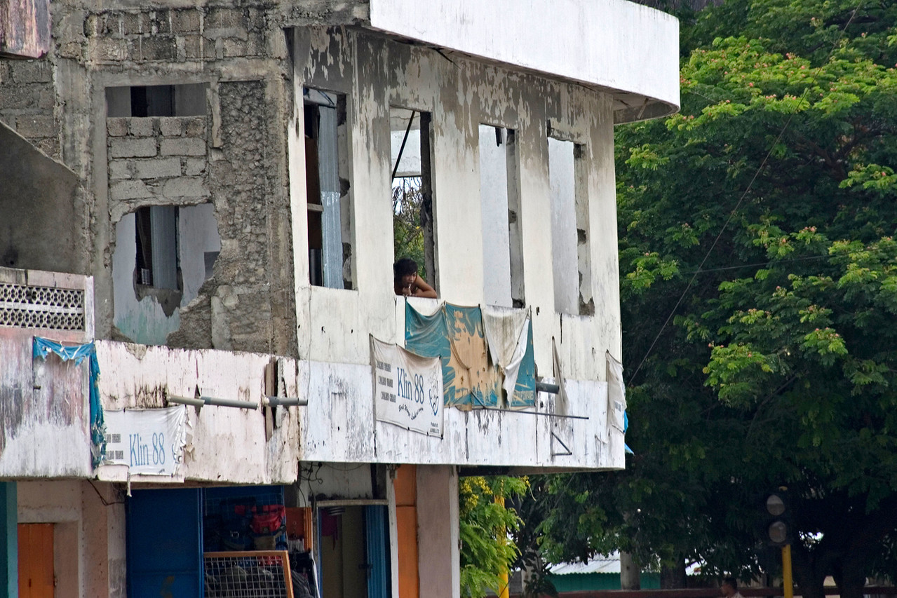 Man in window of an old, dilapidated structure in Dili, East Timor