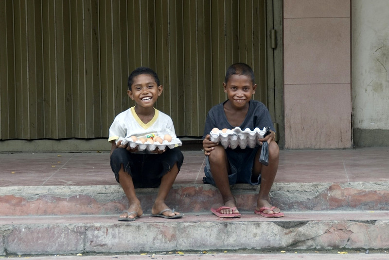 Kids holding an egg tray while seated on a side street at Dili, East Timor