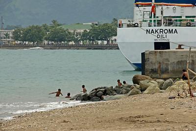 Kids swimming near a boat in Dili, East Timor