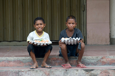 Kids selling eggs at a street in Dili, East Timor