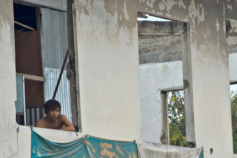 Man looking down a window of an old structure in Dili, East Timor