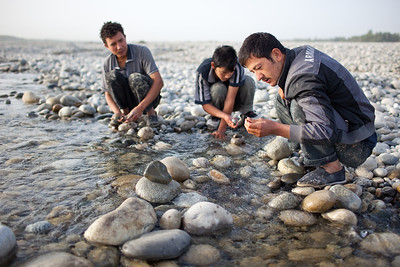 Young men looking for jade in river near Hotan, Xinjiang, China.