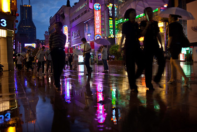 Shanghai, China - September 3, 2009: Shopper on a rainy night on East Nanjing Road, the most polular shopping street in Shanghai and is partially blocked to traffic.  (Photo by: Christopher Herwig)