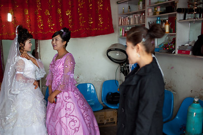 Kucha, China - September 23, 2009: Young Uyghur bride and her bridesmaid getting their hair and makeup done in a salon before the wedding. (Photo by: Christopher Herwig)