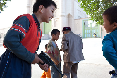 Kucha, China - September 23, 2009:  Young boys playing in the street. (Photo by: Christopher Herwig)