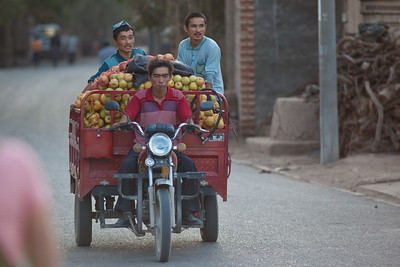 Motorbike with wagon transporting apples in Turpan, China.