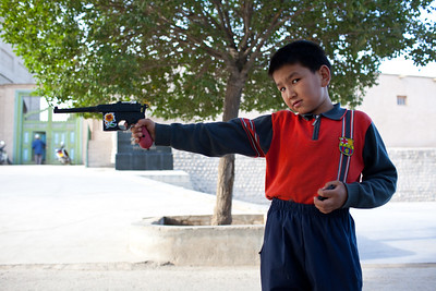 Kucha, China - September 23, 2009:  Young boy playing with a gun in the street. (Photo by: Christopher Herwig)
