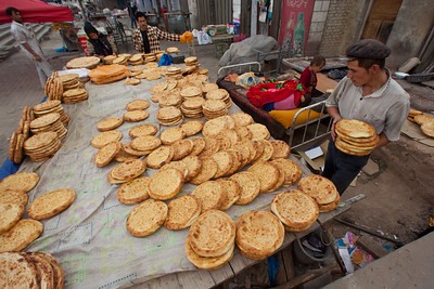 Young man baking bread in Kucha, Xinjiang, China.
