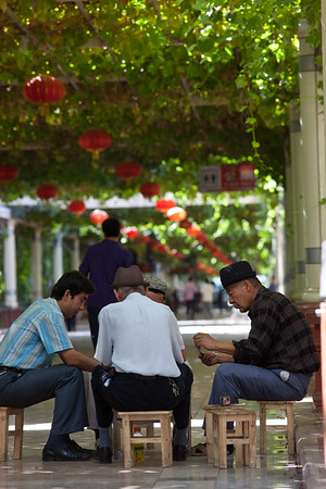 Men playing cards under a grape trellis  which covers some of the downtown streets in Turpan providing much needed shade from the hot sun.