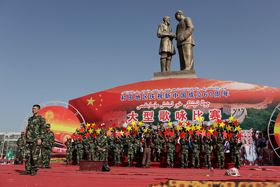 Hotan, Xinjiang, China - September 29, 2009: Chinese soldier in front of a communist propaganda statue of Chairman Mao shaking hands with a shorter Uyhgur man. After riots in Urumqi in July of 2009 the government put thousands of soldiers on the streets of every town in Xinjiang to strengthen their control. Soldiers forced these images to be erased after they were taken. (Photo by: Christopher Herwig)