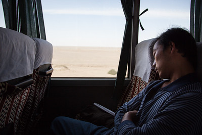 Man sleeping on a bus crossing the desert in China near Dunhuang.