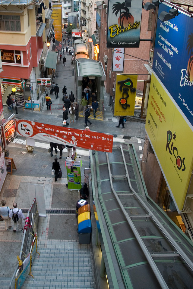 Outdoor escalator looking down on a busy street in Hong Kong