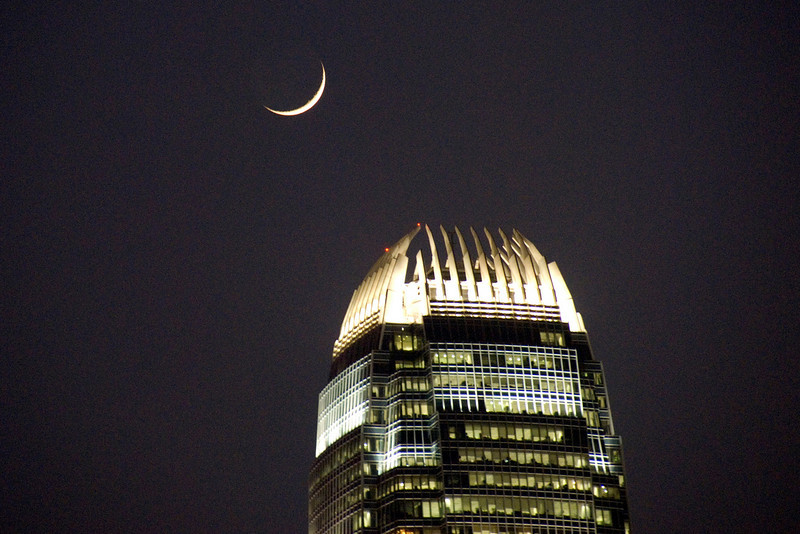 Beautiful shot of the moon towering above the International Finance Center in Hong Kong