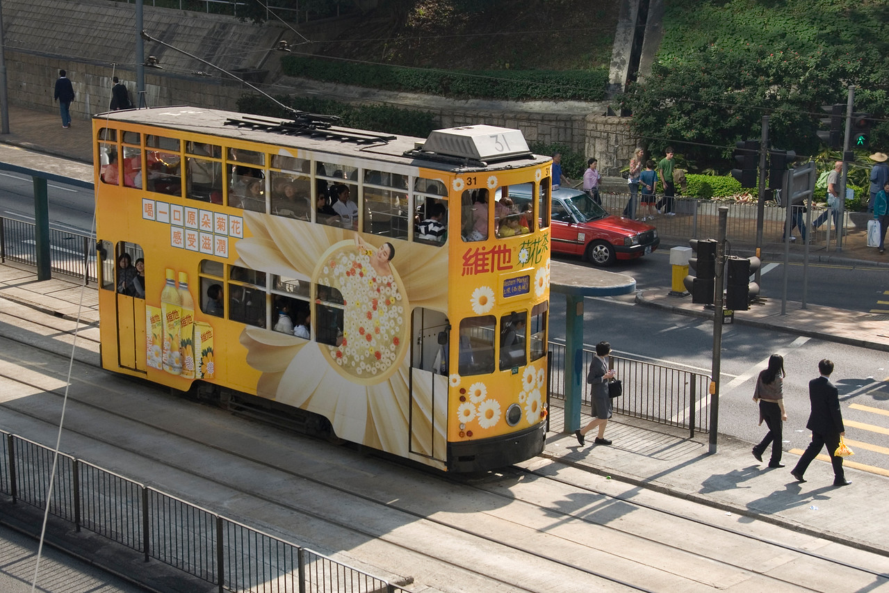 Street trolly carrying passengers while traveling the streets of Hong Kong