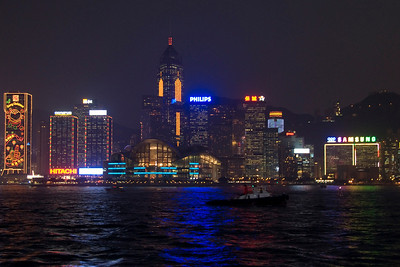 Colorful lights reflected on the water at Victoria Harbor with Hong Kong skyline