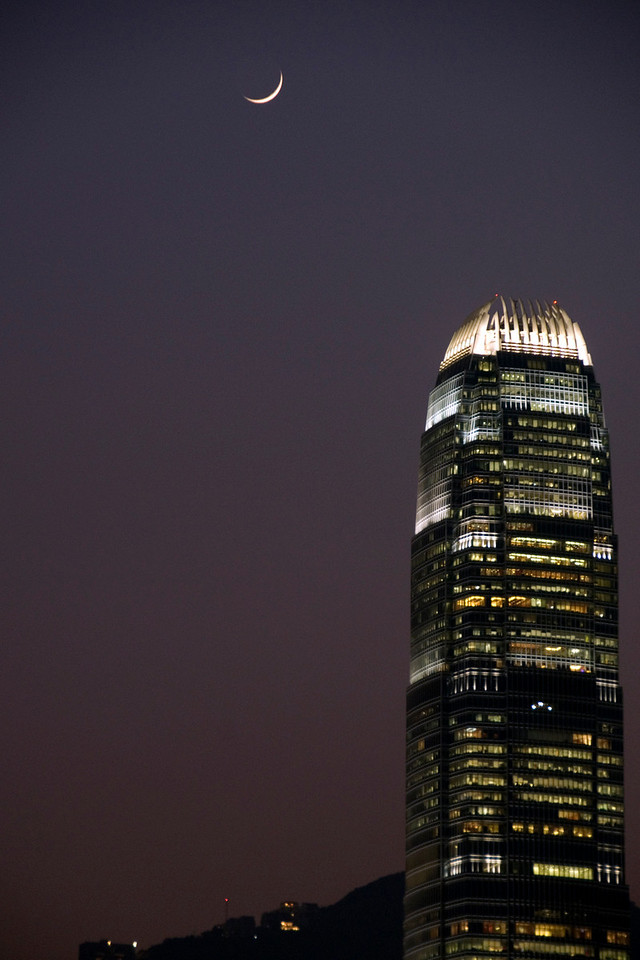 Beautiful shot of the moon over the International Finance Center building in Hong Kong