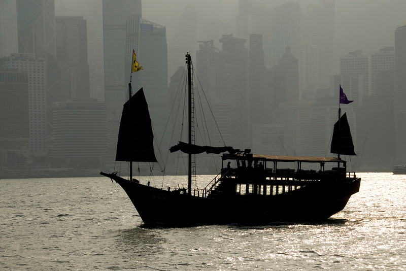 Silhouette of Junk in Victoria Harbor with the Hong Kong skyline as backdrop