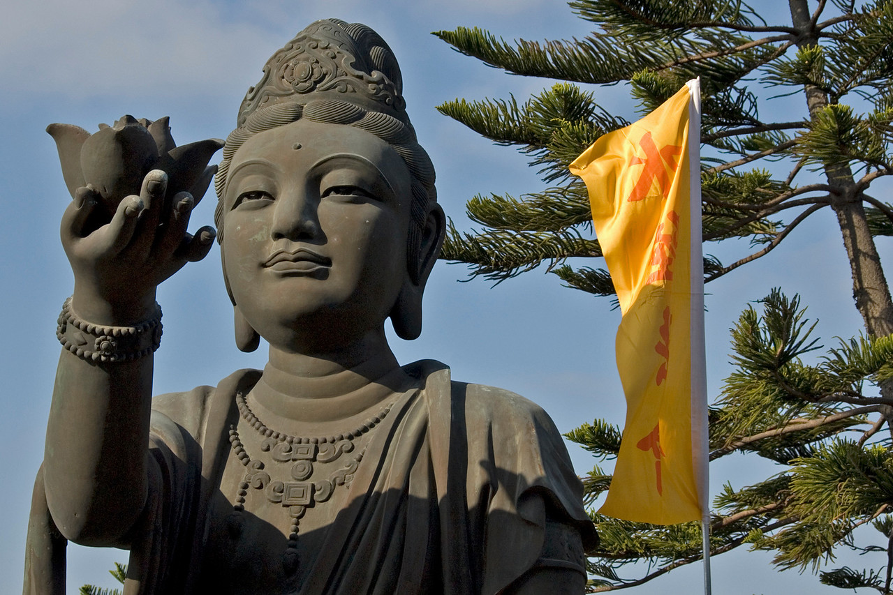 Waving flag beside Big Buddha statue at Po Lin Temple in Hong Kong