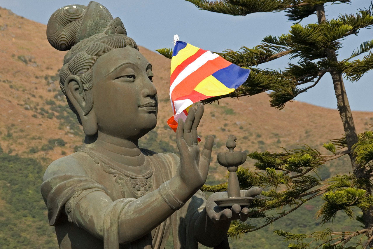 Statue of Big Buddha with flag waving in Po Lin Temple