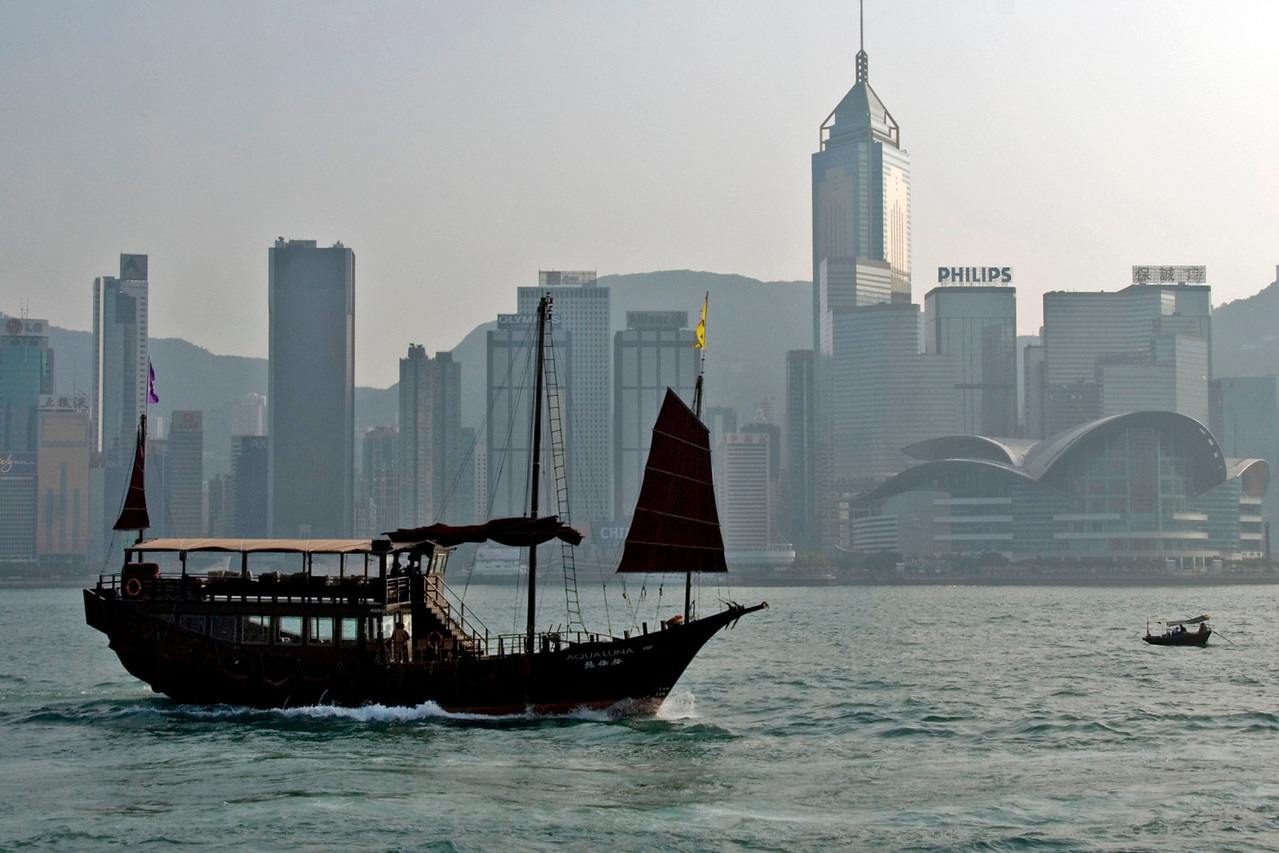 Two boats cruising the Victoria Harbor with the city skyline as backdrop