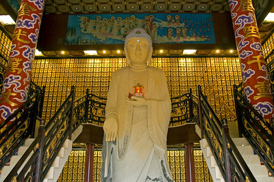 Large white Buddha statue in the middle of stairways inside the 10,000 Buddhas Temple