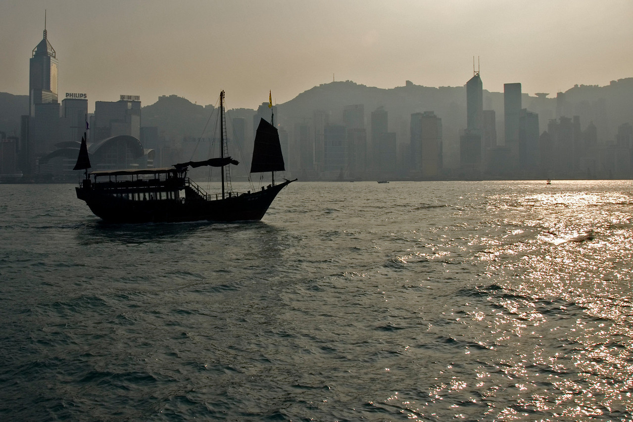 Sun beam on water with junk cruising the Victoria Harbor in Hong Kong