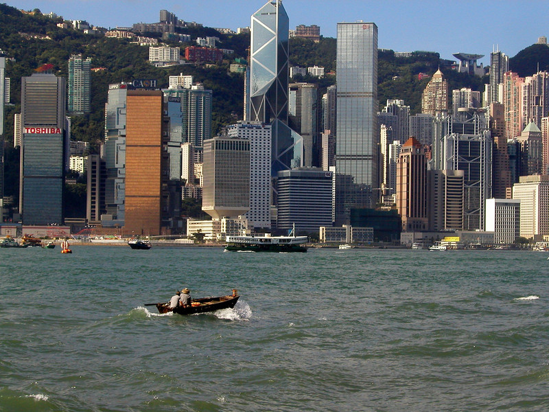 Hong Kong Island skyline from Kowloon and a skiff making it's way in the channel - Aug 2002