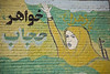 Garmeh, Iran - February, 2008:Mural of a young muslim woman wearing a headscarf and carrying a machine gun.  (Photo by Christopher Herwig)
