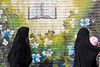 Yazd, Iran - February, 2008: Iranian women in black walking past a mural of the Koran and flowers. (Photo by Christopher Herwig)