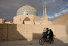 Yazd, Iran - February, 2008:Couple on a motorbike ride past the eleborately tiled 14th century Jameh (Friday) Mosque with 48 meter high minarets in the old town in Yazd, Iran. (Photo by Christopher Herwig)