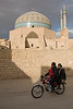 Yazd, Iran - February, 2008: Family on a motorbike ride passed the eleborately tiled 14th century Jameh (Friday) Mosque with 48 meter high minarets in the old town in Yazd, Iran. (Photo by Christopher Herwig)