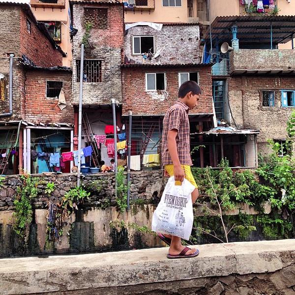 A boy strolls the edge of a slum canal - Mahim, Mumbai