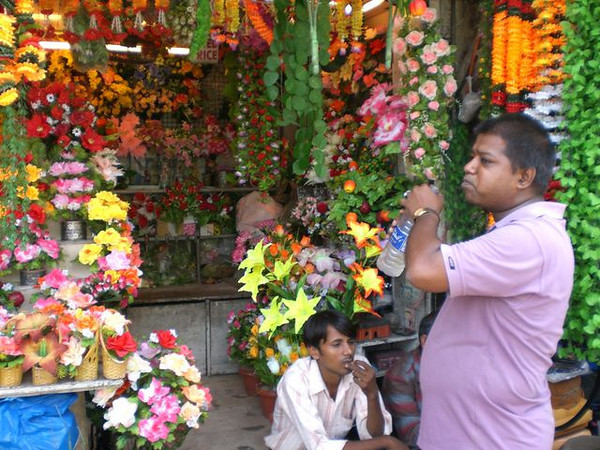 Workers grabbing a drink of water outside of their flower shop.