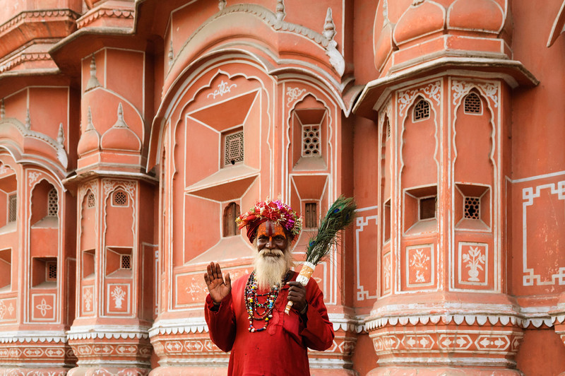Sadhu poses in front of Jaipur Palace of the Winds