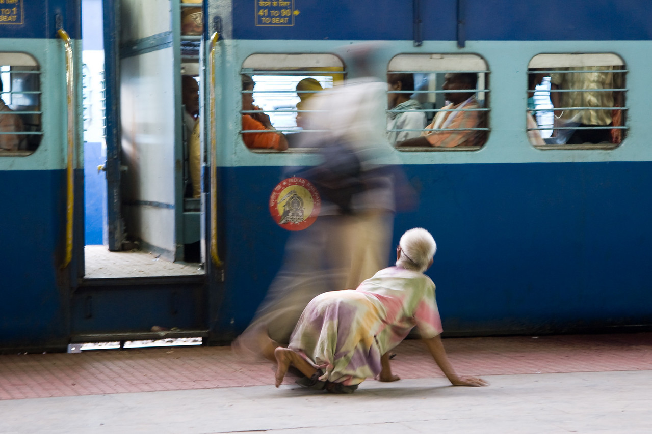 A woman crawls around a train station platform, begging.<br /> <br /> Though not a well focused or sharp photograph, I like the 'glimpse of real life'-aspect of it, especially the blurred passerby ignoring the beggar woman as she scopes out possible donors.<br /> <br /> Location: Varanasi, India<br /> <br /> Lens used: 24-105mm f4.0 IS