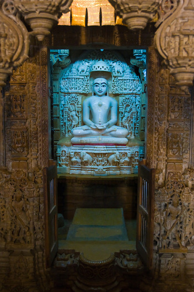 Image of a 'Tirthankara' (enlightened ascetic) from within the inner-sanctum of a Jain temple.<br /> <br /> In Jainism, a religion and belief-system that originated in India but has since spread around the world, every living soul is potentially divine.  When the soul sheds its karmic bonds completely, it attains God-consciousness.  It prescribes a path of non-violence to progress the soul to this ultimate goal.   [excerpt from wikipedia]  This belief is a concept much different than that found in Christianity, Islam and Judaism.<br /> <br /> Jain temples in India are typically marked by extensive and amazingly intricate stone carvings.<br /> <br /> Location: Jaisalmer, India<br /> <br /> Lens used: 17-40mm f4.0