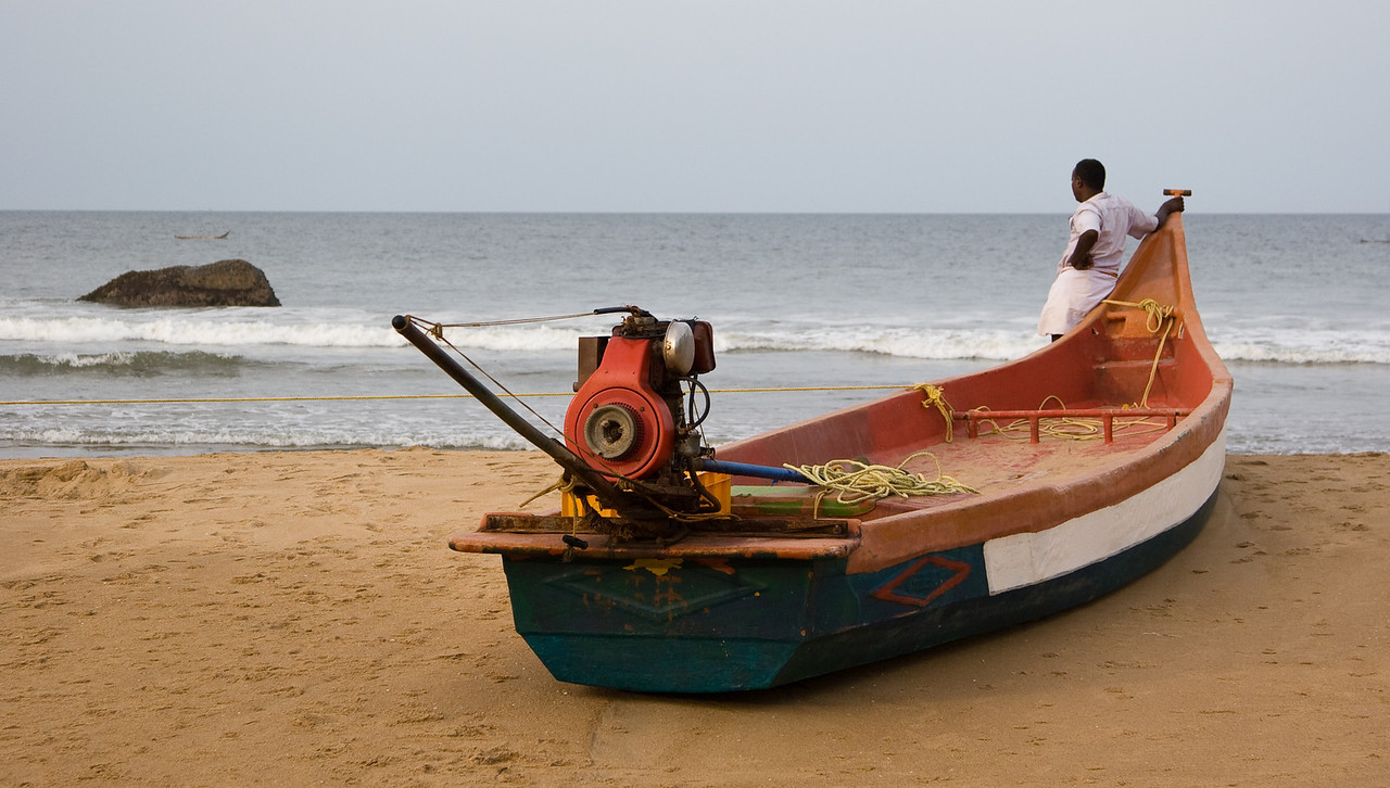 Some people are just drawn toward the sea and fishing.  Here a man stands by a beached fishing boat and longingly eyes the Indian ocean.<br /> <br /> Location: Mamallapuram, India<br /> <br /> Lens used: 24-105mm f4.0 IS