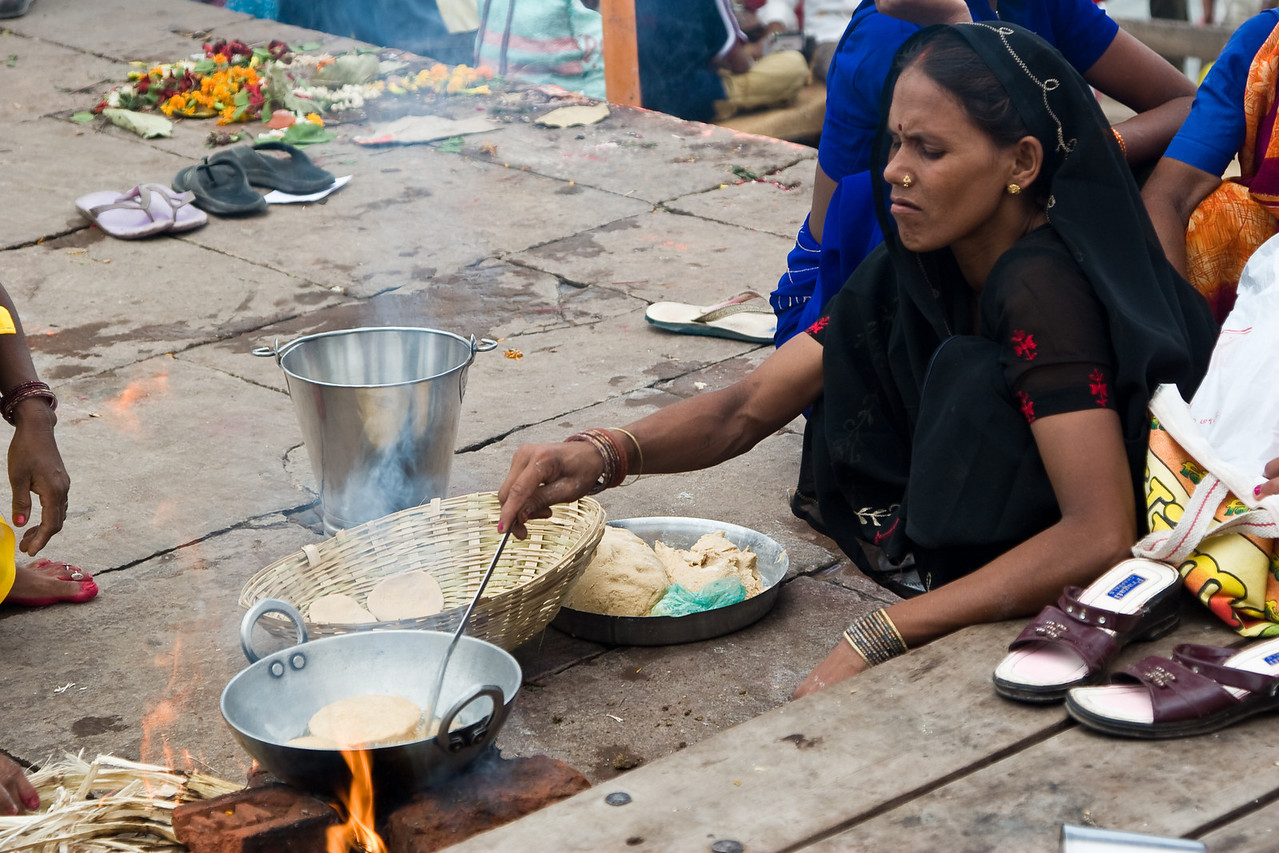 A peasant woman cooks lunch on the ghats in the baking-hot mid-day heat.<br /> <br /> Location: Varanasi, India<br /> <br /> Lens used: 24-105mm f4.0 IS
