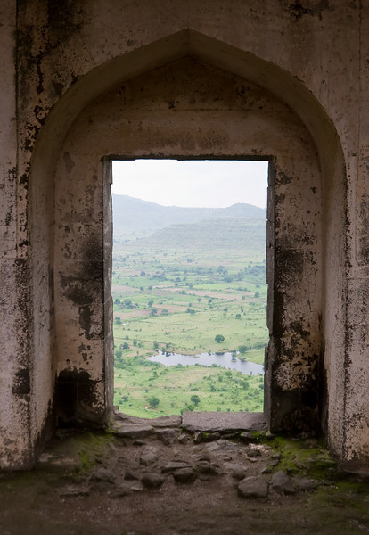 The central Indian countryside as seen through a doorway in an abandoned palace.<br /> <br /> The arched, cupola-shape is extremely common in Indian architecture and is found throughout old buildings and monuments of differing ethnic groups and time periods across the country.<br /> <br /> Location: Daulatabad, India<br /> <br /> Lens used: 28-135mm f3.5-5.6 IS