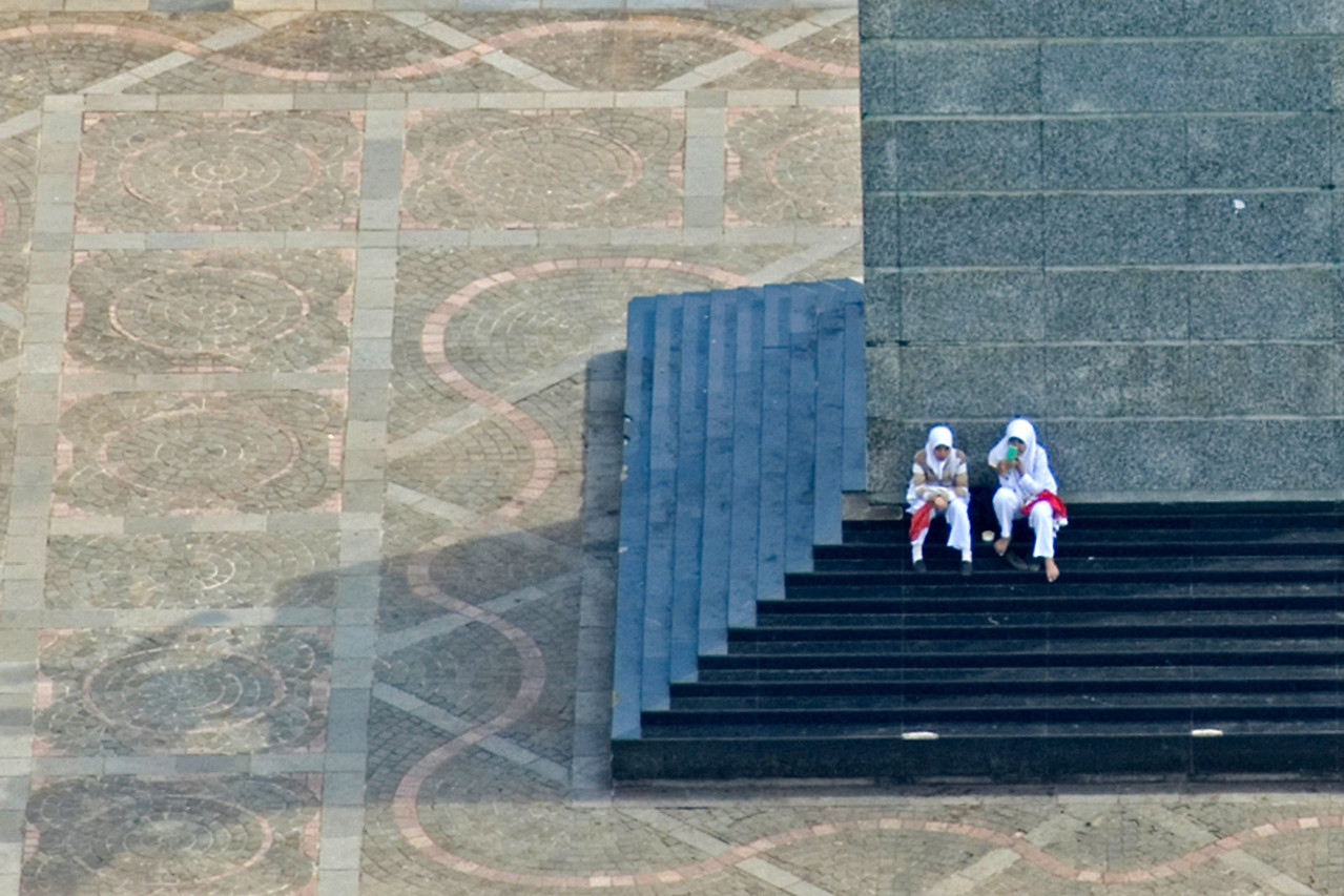Two girls sitting outside the National Monument in Jakarta, Indonesia