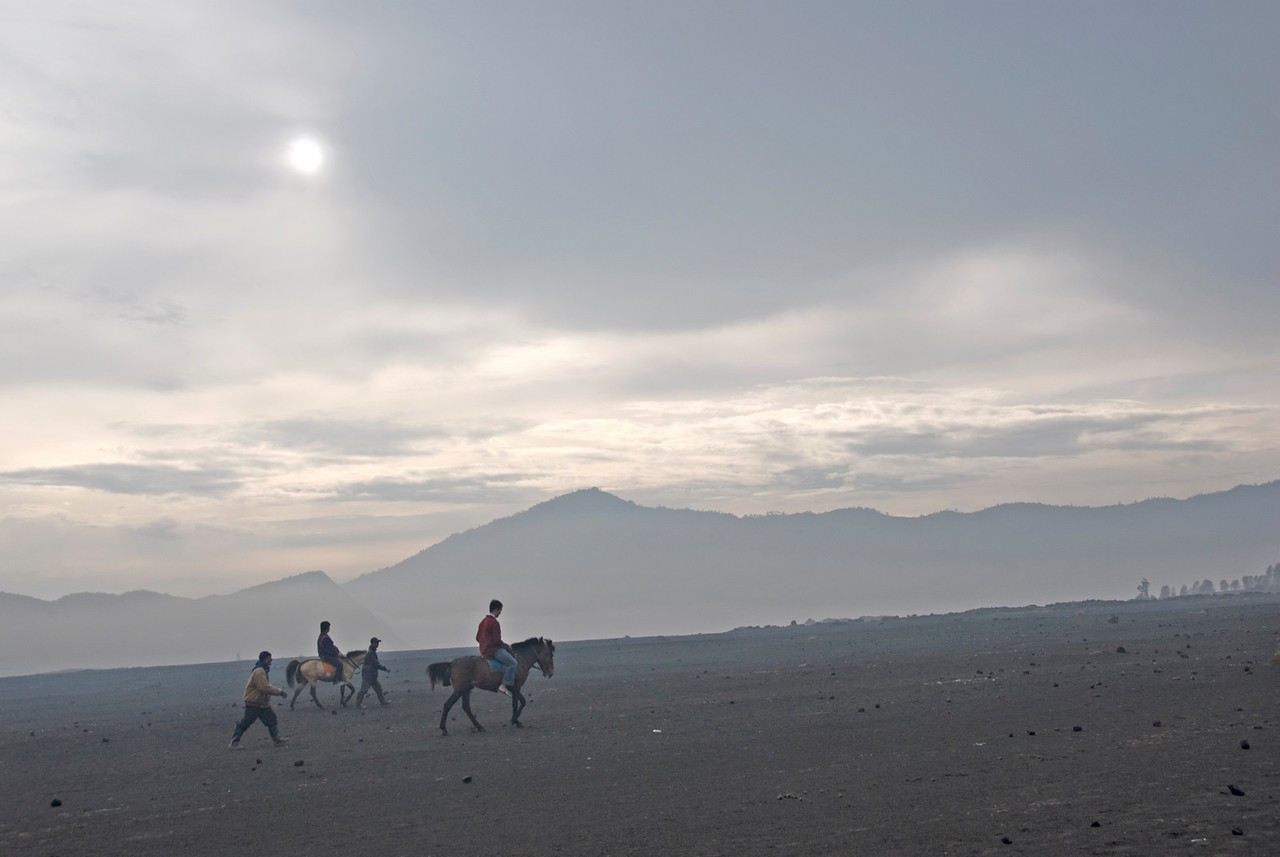 Men riding on horseback near the Mount Bromo crater
