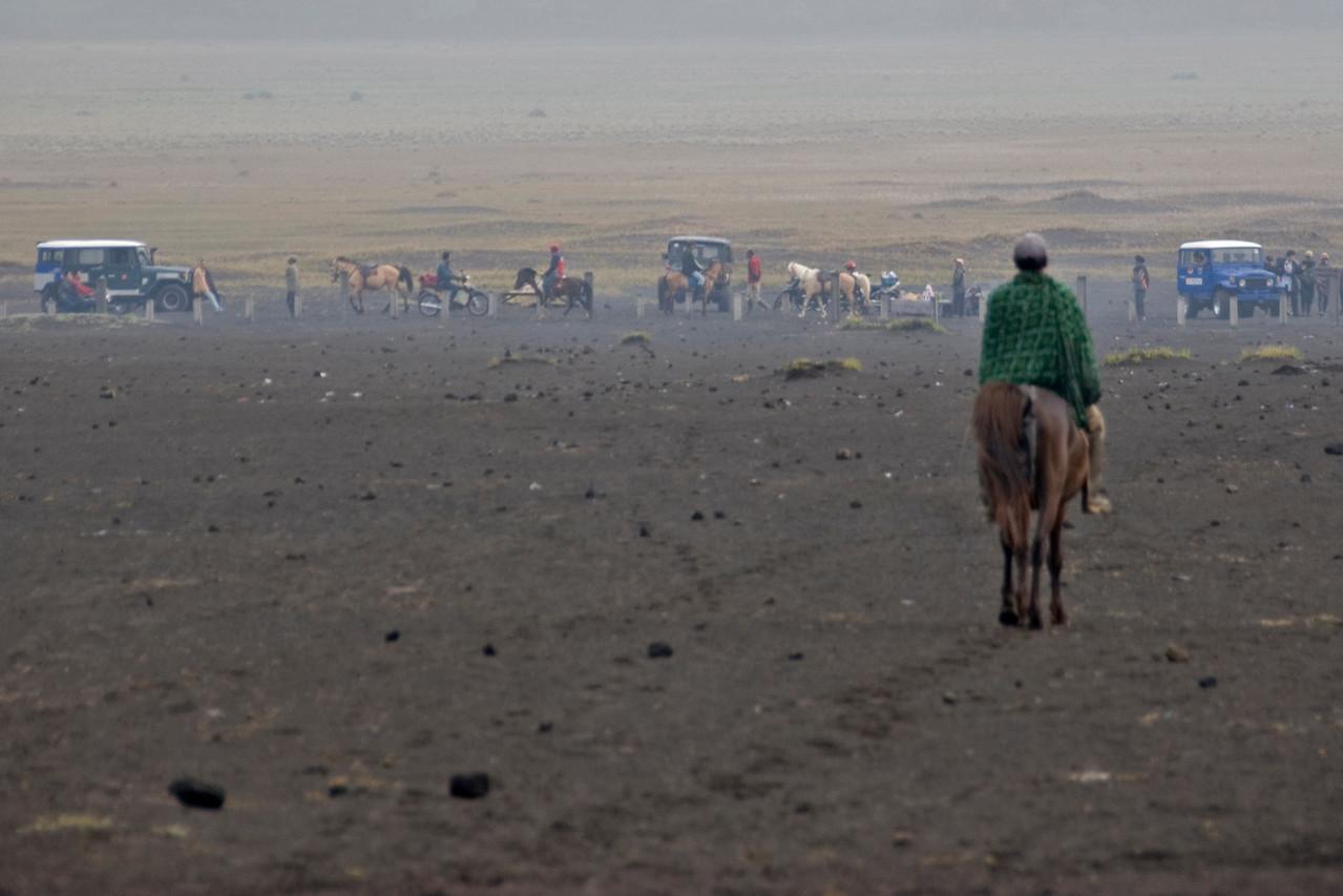 Man on horseback in foreground at Mount Bromo crater