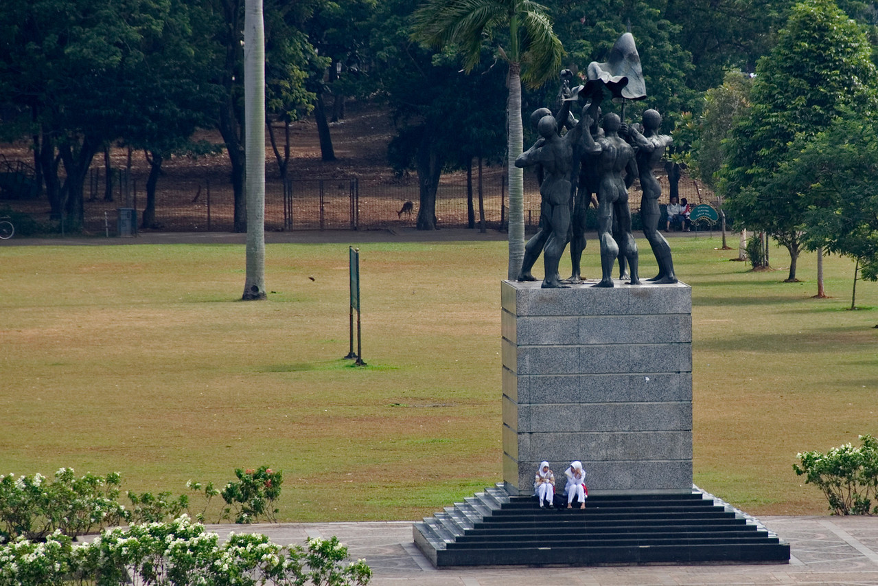 Girls sitting at the National Monument in Jakarta, Indonesia