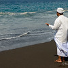 A priest prays during ocean side ceremony
