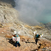 Workers carry sulphur at Ijen Crater