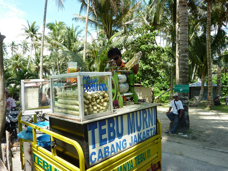 Next to a beach on Batam Island, this man was grinding sugarcane through a press to make juice for beachgoers.