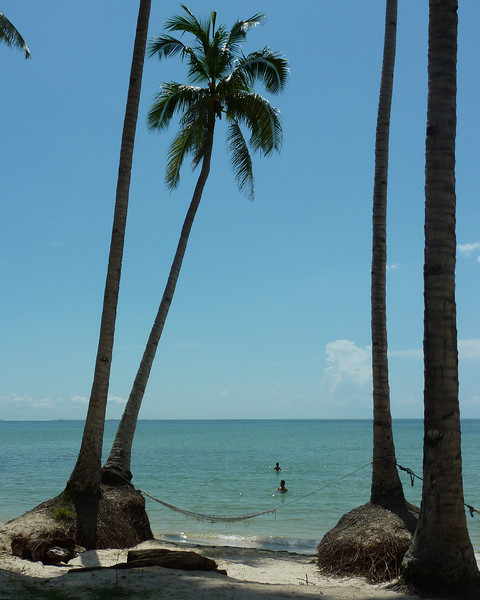 Local Indonesians swimming at a quiet beach. A hammock is there for rest afterwards.