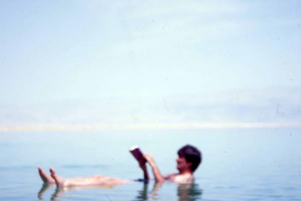 """Det obligatoriske Dødehavsbildet. Fotografen leser Footprint Handbook's Israelsguide. Selv om det sikkert også stod i boken, var det først ved eget øyesyn jeg oppdaget at Dødehavet faktisk er to dødehav, et nordlig og et sørlig. """"Havet"""" har delt seg i to pga. vannmangel, og snart (i historisk perspektiv) vil Dødehavet dø ut og bare eksistere som mange små dødedammer spredd over en lengre strekning i bunnen av Jordan-dalen. (Foto: Geir)"""