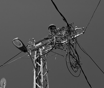 """An electrical """"rat's nest"""" on top of a metal pole.  A sign at the base says, """"Danger of Death."""""""